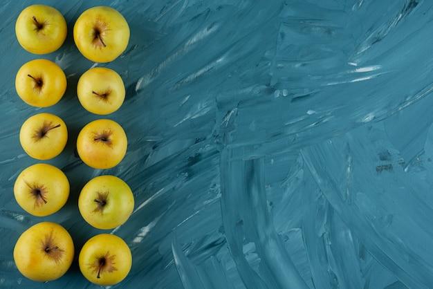 Zbiór świeżych owoców żółte umieszczone na niebieskim tle.