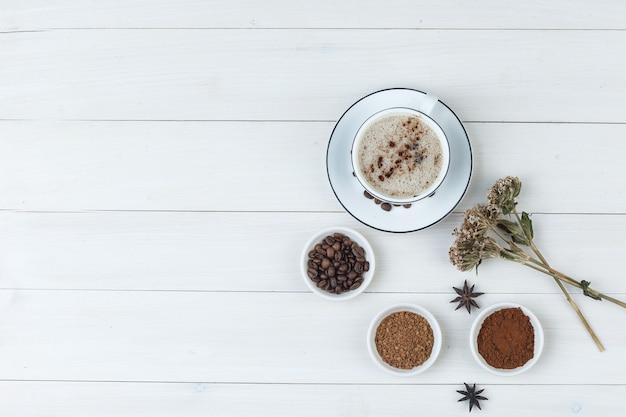 Zbiór ziaren kawy, kawa mielona, przyprawy, ciasteczka, suszone zioła i kawa w filiżance na podłoże drewniane. widok z góry.
