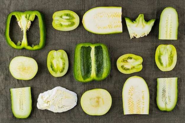 Zbiór zielonych warzyw i owoców na naturalnym materiale. zestaw świeżych zielonych warzyw. papryka, pomidory, ogórek, kapusta, cukinia i jabłko dla wegan. widok z góry