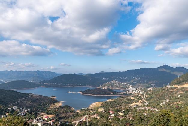Zbiornik pod błękitnym niebem i białymi chmurami otoczony jest górami i lasami