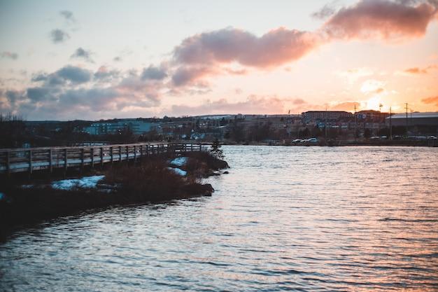Zbiornik wodny w pobliżu mostu pod zachmurzonym niebem w ciągu dnia
