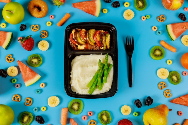 Zbiornik z lunchem na tle świeżych owoców i warzyw.
