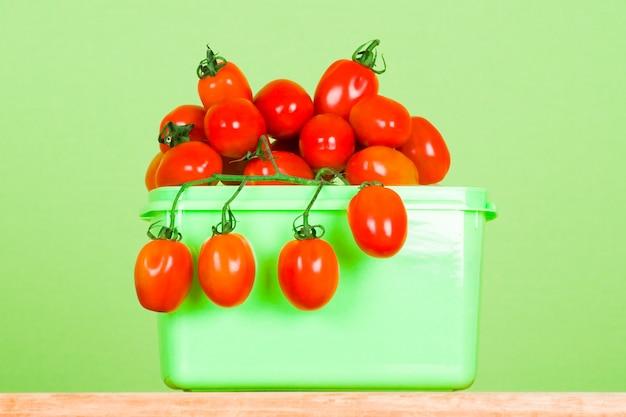 Zbiornik z świeżymi pomidorami na zielonym tle