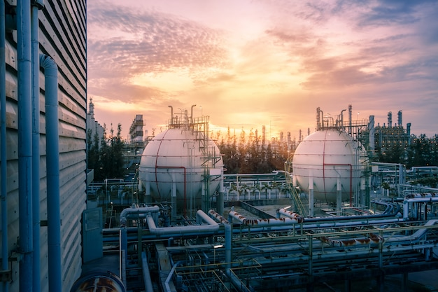 Zbiorniki gazu kuli i rurociągi w petrochemicznym zakładzie przemysłowym na tle zachodu słońca na niebie, produkcja zakładu przemysłu naftowego