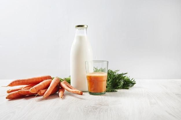 Zbiory marchwi z gospodarstwa ekologicznego leżące obok butelki z mlekiem i szklanką do połowy wypełnioną naturalnym świeżym sokiem na śniadanie.