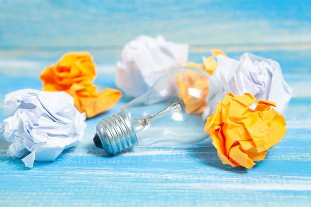 Zbitki papieru i żarówka na stole
