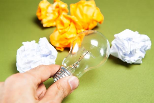 Zbitki papieru i żarówki na zielonym tle. pomysły koncepcyjne
