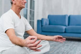 Zbliżenie dłoni mężczyzny z gestem mudra w domu