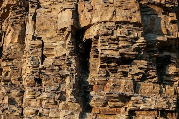 Zbliŝona, kamienista ściana z warstwową nierówną wydrąŝoną powierzchnią.