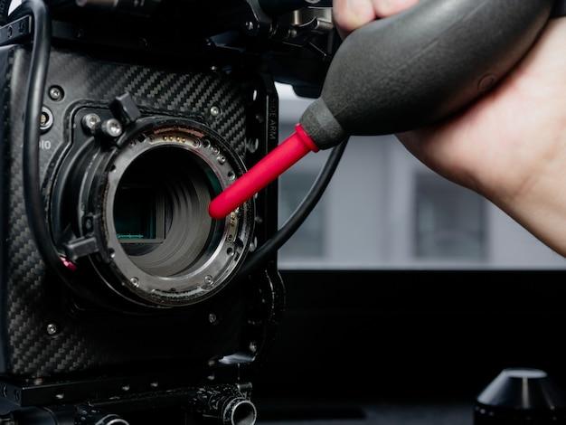 Zbliż ludzką rękę za pomocą gumowego nadmuchiwacza, zdmuchnij kurz i wyczyść szybkę czujnika kamery.