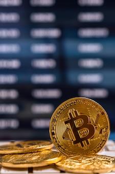 Zbliżenia bitcoins mockup na klawiaturze nad cryptocurrency handlu wykresem w ekranie komputerowym