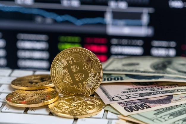 Zbliżenia bitcoins mockup na klawiaturze z pieniądze papierowym bankiem nad cryptocurrency handlu wykresem