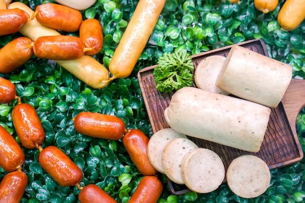 Zbliżenia i uprawy rozmaitości niemiecka kiełbasa z drewnianą tacą na dekoraci zielonej trawy plastikowym tle.
