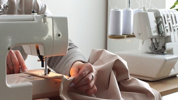 Zbliżenia kobiecych rąk do szycia bawełny za pomocą maszyny do szycia