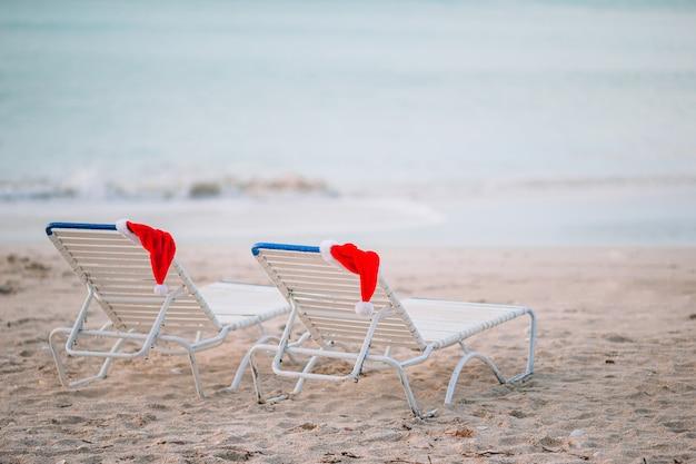 Zbliżenia santa kapelusz na krześle na tropikalnej biel plaży