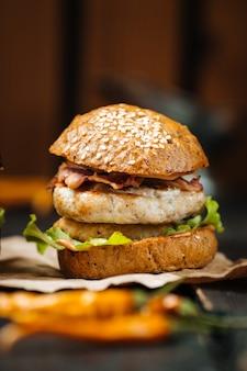 Zbliżenia smakowitego chiken hamburgeru ciemny drewniany stół