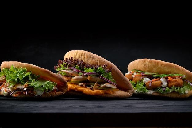 Zbliżenia trzy różne apetyczne kanapki lub hamburgery na drewnianej powierzchni