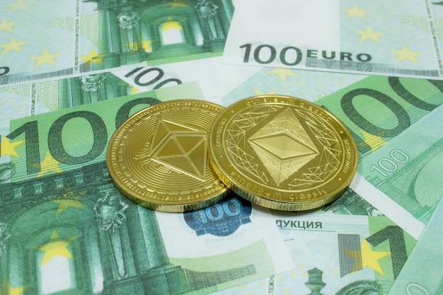 Zbliżenie 2 monet ethereum na banknotach 100 euro. kryptowaluta etc.
