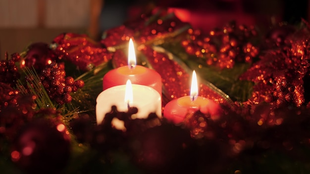 Zbliżenie 4k materiał trzy czerwone i białe świece płonące w boże narodzenie wieniec adwentowy w nocy. idealne tło lub tło na boże narodzenie lub nowy rok