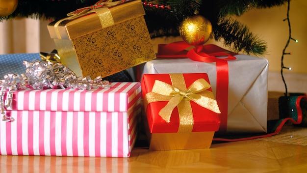 Zbliżenie 4k panoramowanie materiał duży stos prezentów i prezentów w pudełkach leżących pod choinką w salonie. idealne zdjęcie na zimowe uroczystości i święta