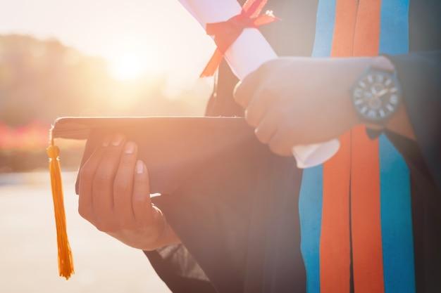Zbliżenie absolwenta uniwersytetu posiadającego dyplom i tablicę do zaprawy murarskiej
