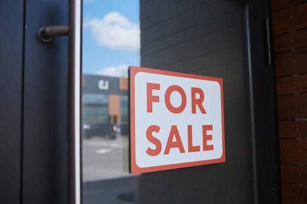 Zbliżenie afisz na sprzedaż wisi na drzwiach nowoczesnego budynku biurowego