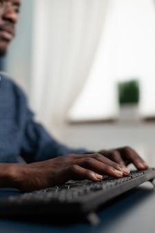 Zbliżenie african american ręce wpisując strategię zarządzania na klawiaturze, pracując w prezentacji biznesowej przy użyciu platformy uniwersyteckiej podczas blokady w salonie. użytkownik komputera w domu
