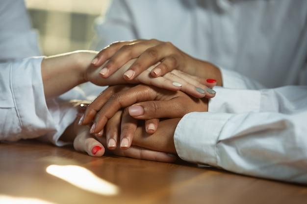 Zbliżenie afro-amerykańskich i kaukaskich rąk człowieka trzymających się na drewnianym stole