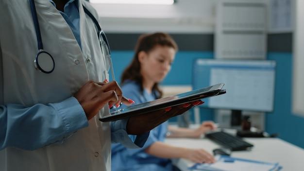 Zbliżenie afroamerykańskiego lekarza za pomocą tabletu z ekranem dotykowym