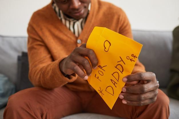 Zbliżenie afroamerykańskiego mężczyzny otwierającego list dla taty jako ręcznie robiony prezent na dzień ojca, miejsce kopiowania