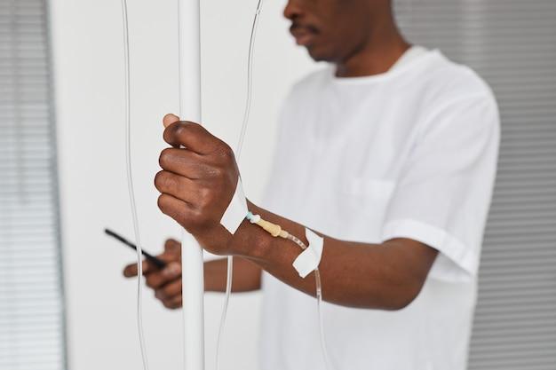 Zbliżenie afroamerykańskiego mężczyzny w sali szpitalnej, skupienie się na dłoni z konfiguracją kroplówki iv, kopia przestrzeń