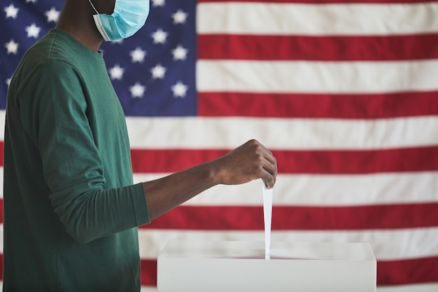 Zbliżenie: afrykanin ubrany w maskę ochronną biorący udział w głosowaniu on wkładając kartę do urny
