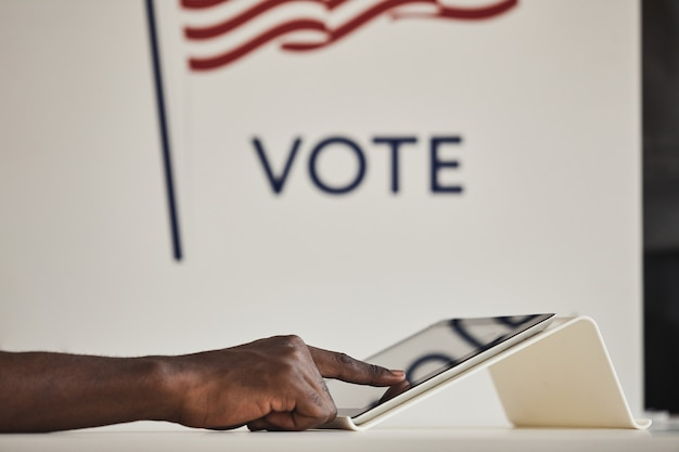 Zbliżenie: afrykański mężczyzna dotyka ekranu komputera podczas głosowania w lokalu wyborczym