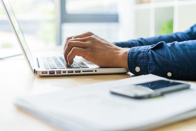 Zbliżenie: afrykański mężczyzna pisania na laptopie.