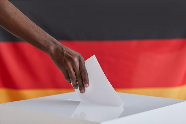 Zbliżenie: afrykański mężczyzna wkładający kartę do głosowania przeciwko niemieckiej fladze podczas głosowania