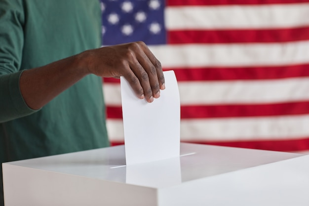 Zbliżenie: afrykańskiego człowieka oddanie karty do głosowania n pola podczas wyborów federalnych