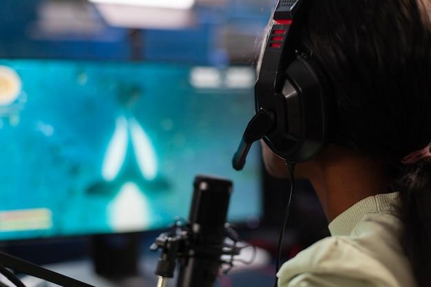 Zbliżenie afrykańskiego gracza e-sportowego online transmituje na żywo zawody w kosmicznej strzelance. streamuj wirusowe gry wideo dla zabawy przy użyciu słuchawek i klawiatury podczas mistrzostw online.