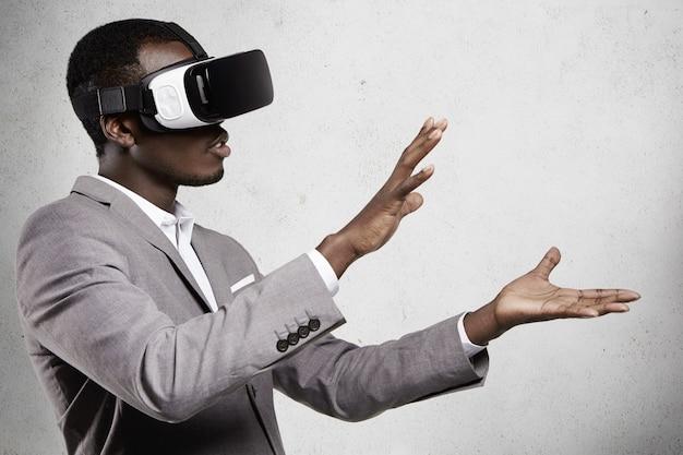 Zbliżenie afrykańskiego pracownika w formalnym garniturze i okularach, doświadczającego wirtualnej rzeczywistości, wyciągającego ramiona, jakby trzymającego coś w dłoniach.