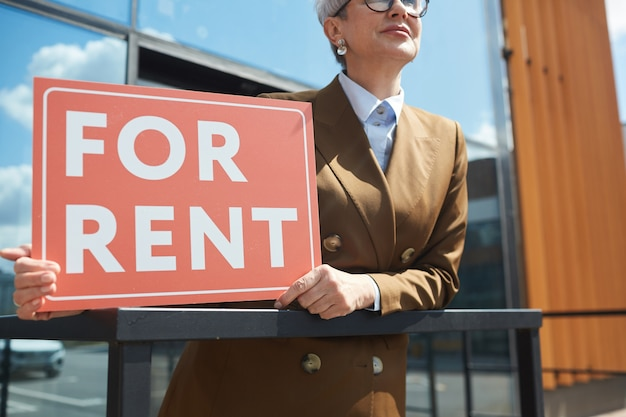 Zbliżenie: agent nieruchomości z tabliczką do wynajęcia stojącego na zewnątrz