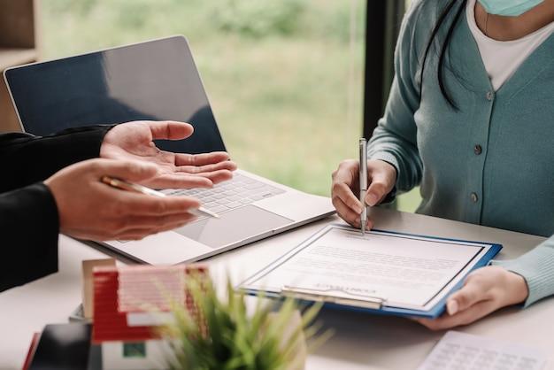 Zbliżenie agenta nieruchomości przekazującego klientowi dokumenty kupna i sprzedaży w celu podpisania umowy o zawarcie umowy w urzędzie.