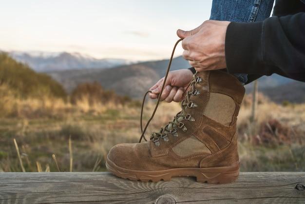 Zbliżenie alpinista wiązanie brązowych sznurówek do butów z zaśnieżonymi górami w ścianie