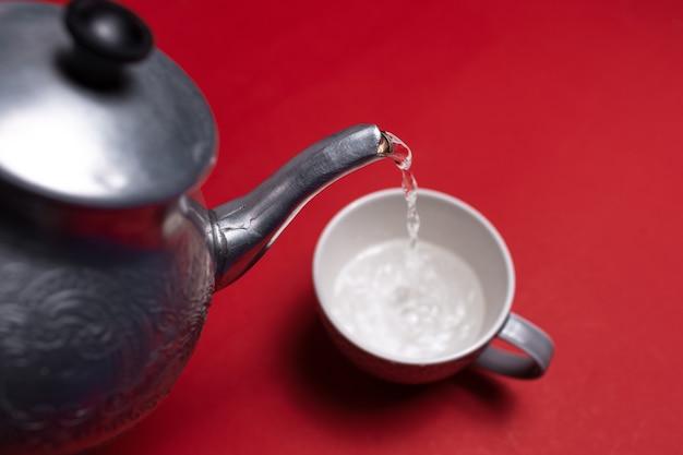 Zbliżenie aluminiowego czajnika wlewającego wodę do ceramicznego kubka na powierzchnię koloru czerwonego
