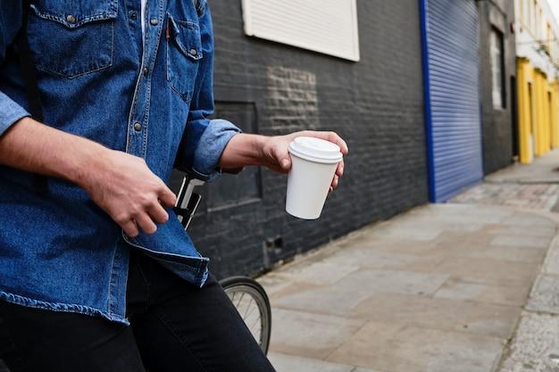 Zbliżenie anonimowy profesjonalny młody człowiek stojący i trzymający filiżankę kawy na zewnątrz.