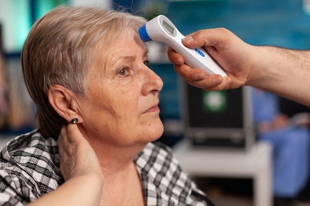Zbliżenie: asystent człowieka pomocnika sprawdzania temperatury za pomocą medycznego termometru na podczerwień, omawiając z starsza kobieta. opieka społeczna opiekująca się starszą emerytowaną kobietą. pomoc zdrowotna