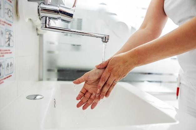 Zbliżenie asystent laboratoryjny do mycia rąk stojąc w laboratorium.