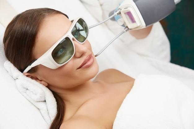 Zbliżenie: atrakcyjna kobieta otrzymująca laserowe odmładzanie w gabinecie kosmetycznym przez kosmetyczkę, dziewczyna robi zabieg na twarz