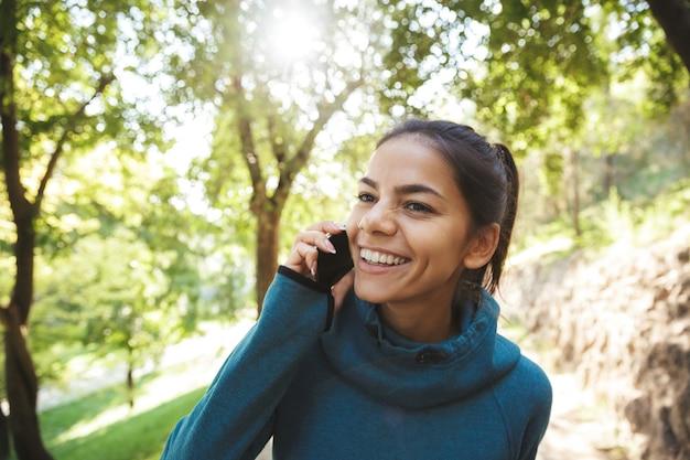 Zbliżenie atrakcyjna młoda kobieta fitness noszenie odzieży sportowej ćwiczeń na świeżym powietrzu, przy użyciu telefonu komórkowego