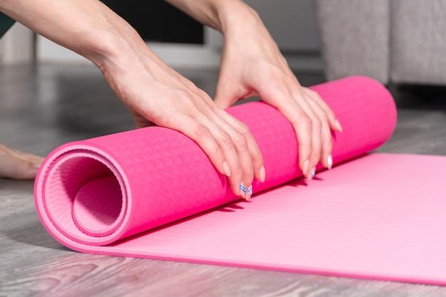 Zbliżenie: atrakcyjna młoda kobieta składana mata do jogi lub fitness po treningu w domu w salonie. zdrowe życie, dbaj o kondycję