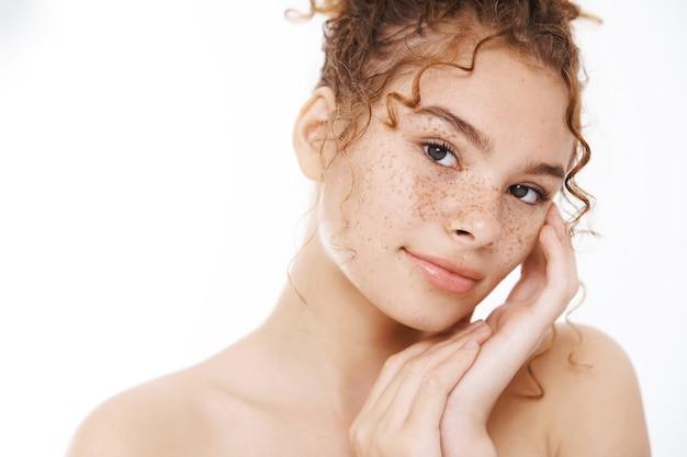 Zbliżenie atrakcyjna naga delikatna ruda kobieta piegi dotyka skóry czule uśmiechający się aparat z ulgą zmysłowo, osiągnięta czysta skóra, prowadzi aktywny, zdrowy styl życia, autentyczne piękno