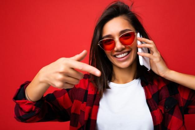 Zbliżenie atrakcyjna pozytywna młoda brunet kobieta ubrana w stylową czerwoną koszulę białą koszulkę i czerwone okulary na białym tle nad czerwonym